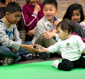 Baby plays with primary school pupils
