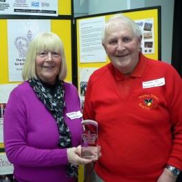 Man and woman display award trophy