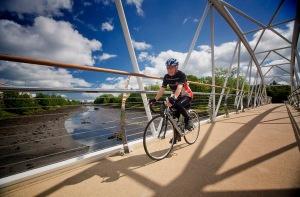 John McKeag cycling across the Sam Thompson Bridge