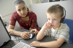 Young woman helping young girl use computer
