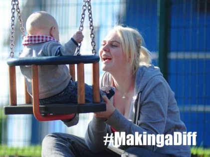 Young mum playing with child on swing