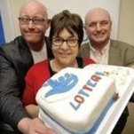 Two men and a woman pose with a Lottery cake