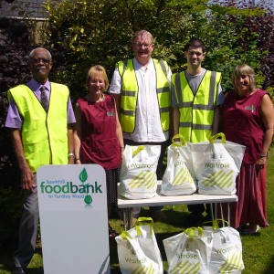 Five Sparkhill food bank staffers with bagged food in front of them