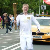 Callum proudly carrying the Olympic Torch