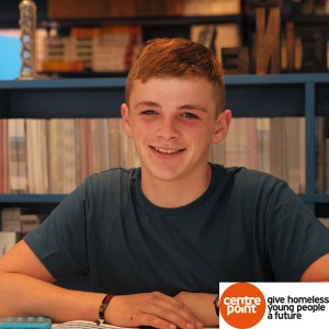 Young man smiling, sitting down at desk