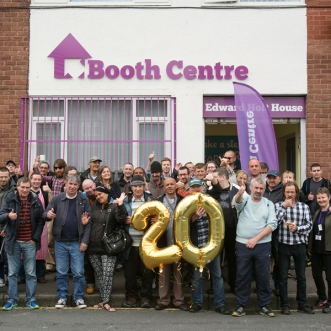 Group of people standing outside the Booth Centre celebrating 20 years