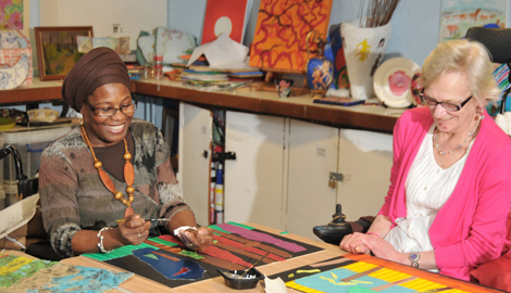 Two woman sitting at a crafts table with big smiles