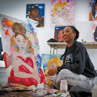 Black woman sitting legs crossed in art studio, smiling