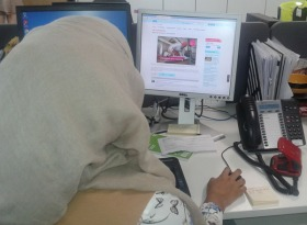 Sanjida from behind sitting at a desk working at PC